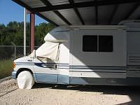 An RV with tire covers and windshield covers in place while being stored under an awning.