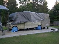RV covered with plastic tarps for weather reasons.