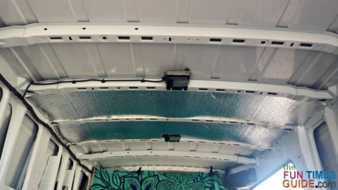 Insulation placed between the ceiling cross-ribs on a cargo van.
