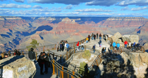 People taking in the view of Grand Canyon from the guardrail.
