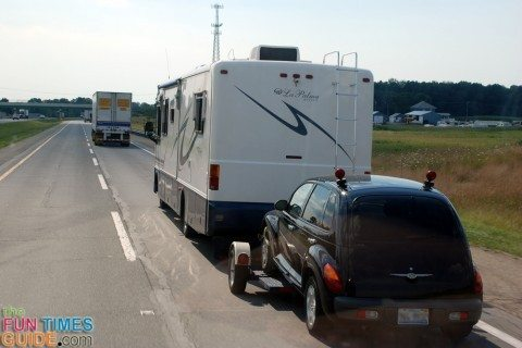 Motorhome towing a car on a dolly