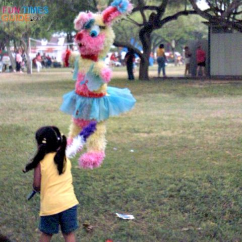 Little girl at Easter picnic hitting the Easter bunny pinata