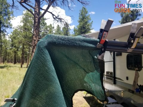 Sun shade clamped to the RV awning rail.